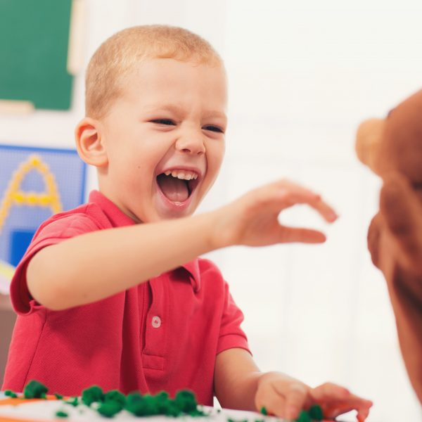 Little boy during lesson with his speech therapist.