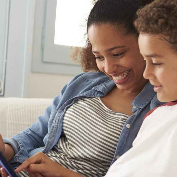 Mother And Son Sitting On Sofa Using Digital Tablet