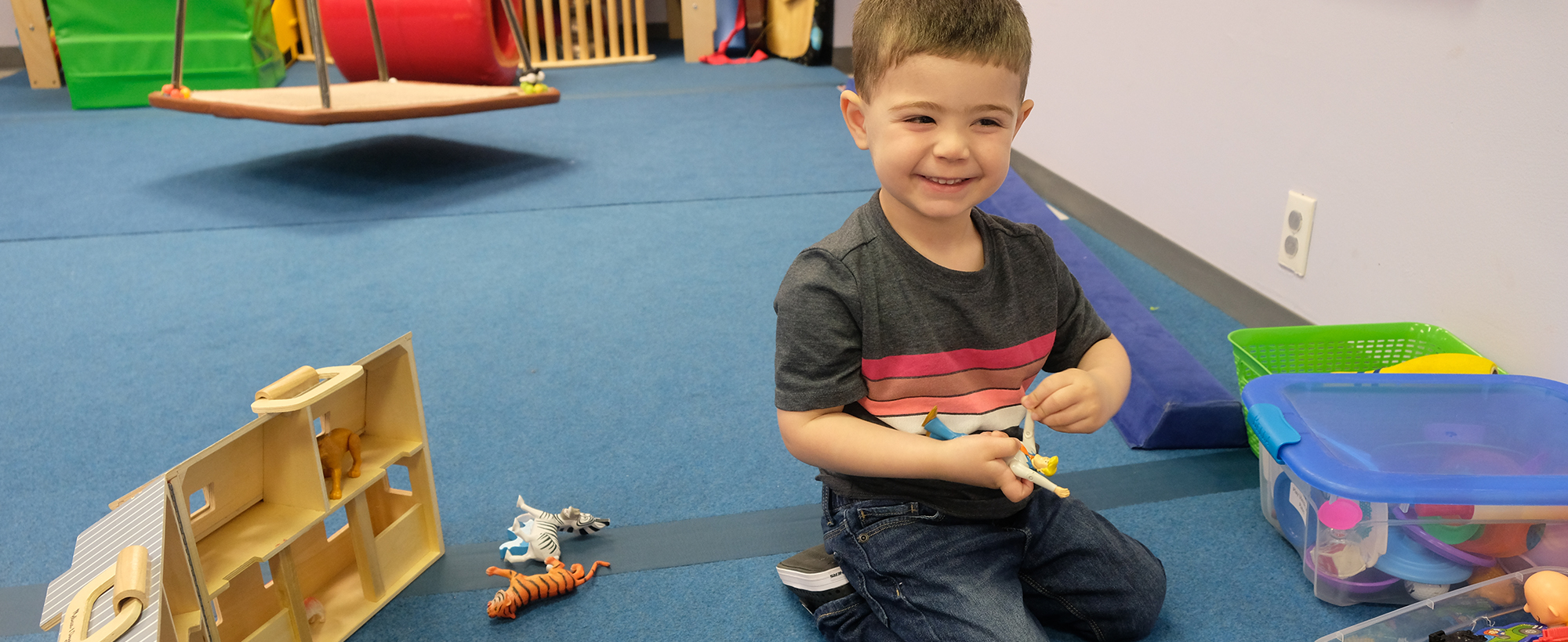 Student playing with toys and smiling
