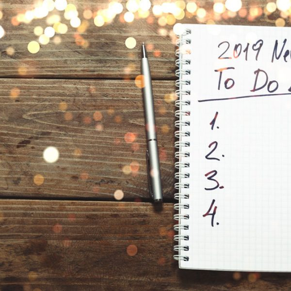 New year 2019 Goals Concept. Notepad with To do list and cup of coffee on wooden table, top view, flat lay